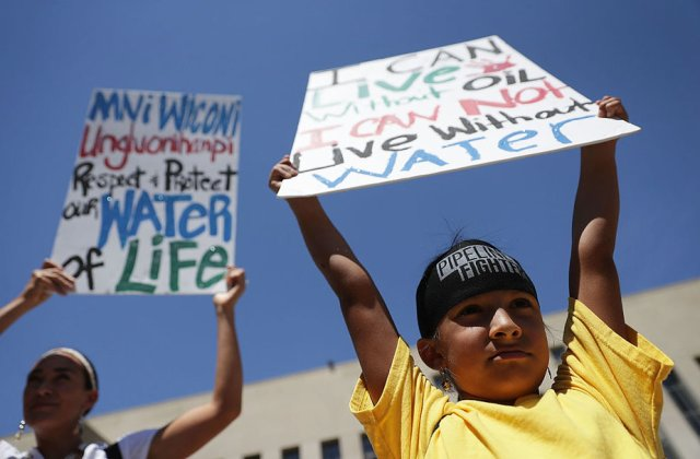 """WASHINGTON, DC - AUGUST 24:  Seven-year-old Omaka Nawicakinciji (R) of the Oglala Lakota Nation in South Dakota participates with his mother Heather Mendoza (L) during a rally on Dakota Access Pipeline August 24, 2016 outside U.S. District Court in Washington, DC. Activists held a rally in support of a lawsuit against the Army Corps of Engineers """"to protect water and land from the Dakota Access Pipeline,"""" and to call for """"a full halt to all construction activities and repeal of all pipeline permits until formal tribal consultation and environmental review are conducted.""""  (Photo by Alex Wong/Getty Images)"""