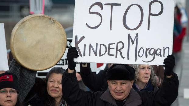 Grand Chief Stewart Phillip, president of the Union of B.C. Indian Chiefs, holds a sign while marching to a protest outside National Energy Board hearings on the proposed Trans Mountain pipeline expansion in Burnaby, B.C., on Jan. 19, 2016.