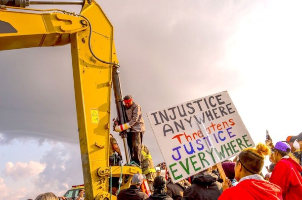 Happy American Horse attaching himself to an excavator at the construction site of the Dakota Access Pipeline on Aug. 31. Rob Wilson / Bold Alliance