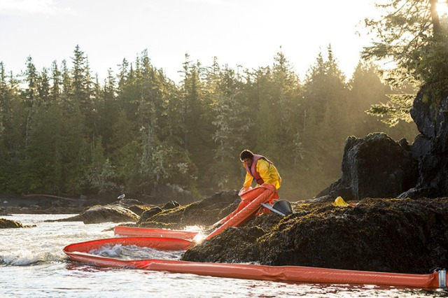 A worker adjusts booms on the rocks near the spill site — image credit: Tavish Campbell